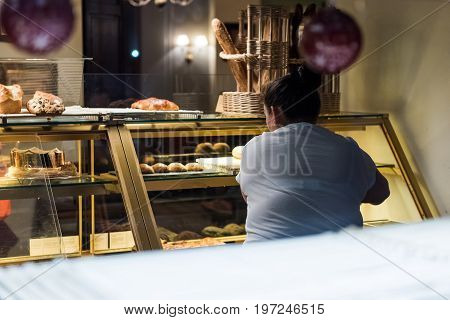 Washington Dc, Usa - December 29, 2016: Woman Selling Baked Goods In Bakery, Viewed From Outside Win