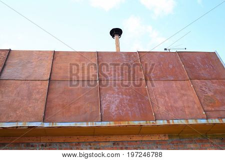 The roof of the country house covered with sheets of rusty metal. Corrosion of metal when exposed to the weather
