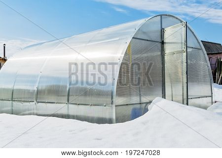Snow-covered greenhouse polycarbonate at their summer cottage. Russia Siberia Novosibirsk region Berdsk