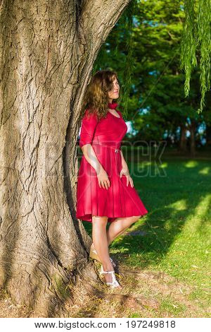 Woman With Long Hair In Red Dress Leaning On Willow Tree By Potomac River In Washington Dc Park