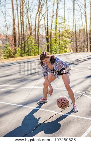 Young Fit Woman Bouncing Basketball In Playground