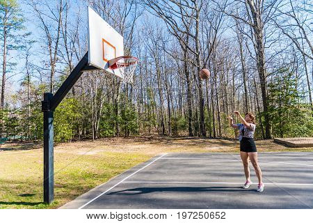 Young Fit Woman Jumping Up Throwing Basketball Into Hoop In Playground