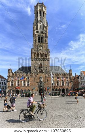 Bruges, Belgium - July 7, 2017: Tourist Riding A Bike In Front Of The Belfry Tower In The Market Squ