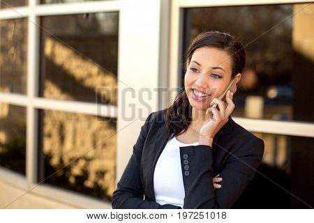 Business woman talking on her mobile phone outside an office bussiness.