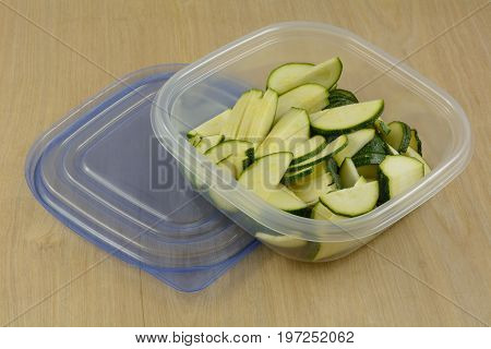 Raw zucchini slices in plastic refrigerator storage containers as part of planning ahead for cooking dinner faster after work