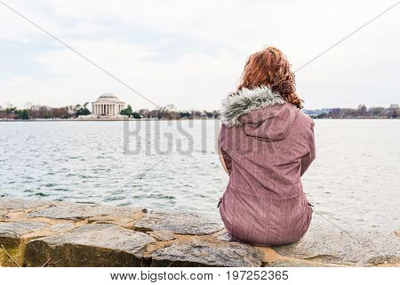 Young Woman Sitting On Edge Looking Over Tidal Basin And Thomas Jefferson Memorial In Park