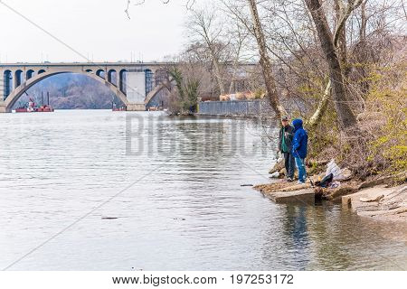Washington Dc, Usa - March 20, 2017: People Fishing On Riverfront In Georgetown With Key Bridge In P