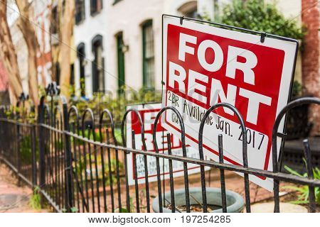Red For Rent sign with details on front porch of house