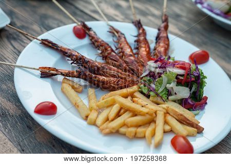 Potato fries with fry prawns and lettuce salad decorated with cherry tomatoes. Isolated over wooden background