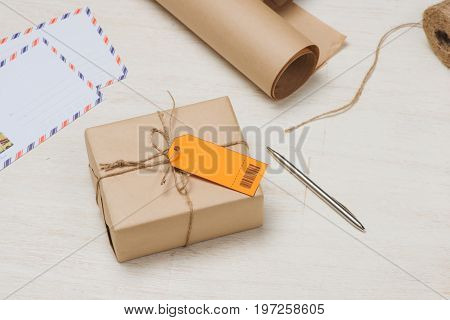 Parcel tied with string with address orange label attached