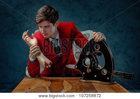 The magician in the red jacket sits at a table with a guillotine and looks at a fake severed hand