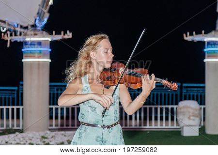 Nahariya Israel July 26 2017 : The young girl in the summer evening plays for passers-by on the violin on the waterfront of Nahariya Israel