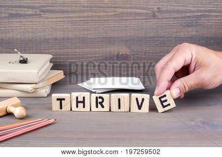 thrive concept.Wooden letters on dark background. Office desk