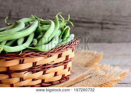 Fresh green beans in a wicker basket and on a wooden board. Unripened green beans, organic source of dietary fiber, vitamins and minerals. Wooden background