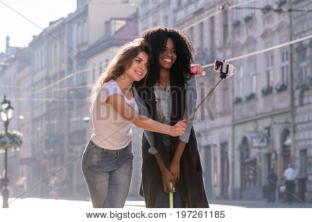 Happy atrractive girls making selfie in the center of the city with nice architecture. One girl is blCK.
