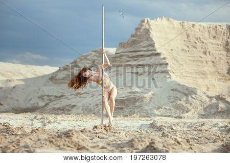 Striptease woman is dancing on a pole in the desert.