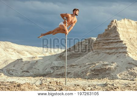 Man is an acrobat on a pole he performs tricks.