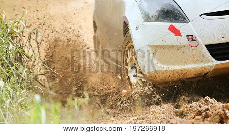 Rally car racing  in muddy road .