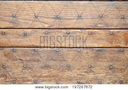 old wooden door detail with studs and diamond pattern