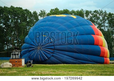 Colorful hot air balloon being inflated on the ground and getting ready for flight