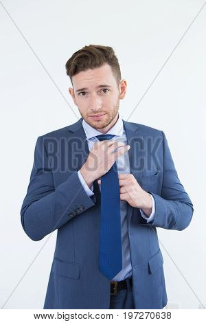 Arrogant handsome young businessman adjusting tie and looking at camera. Serious confident male executive getting dressed. Elegance concept