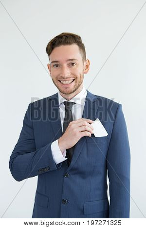 Cheerful successful handsome businessman putting blank card into jacket pocket and looking at camera. Ambitious young consultant standing opposite white background. Individual concept