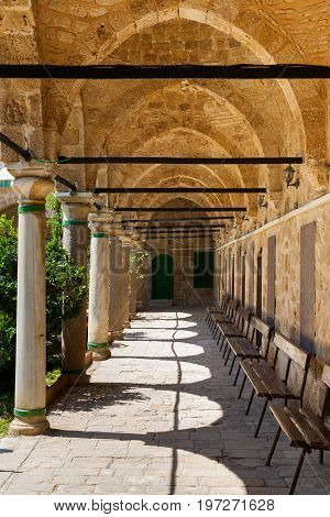 Columned Portico With Stone Pillars And  Wooden Benches In Mosque In Acri Akko Israel