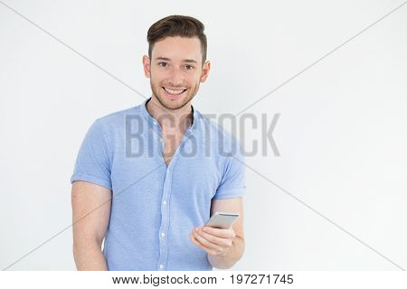 Cheerful young male manager with gadget looking at camera. Smiling handsome young man using mobile app on smartphone. Gadget concept