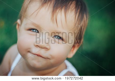 baby smiling and looking up to camera outdoors in sunlight