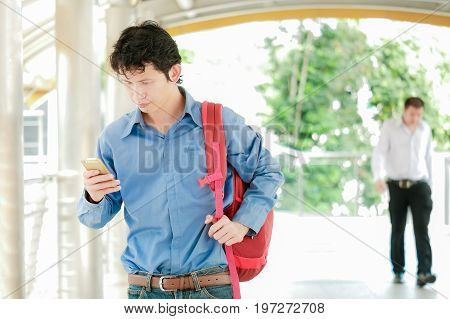 Businessman or tourist holding mobile using smartphone for texting sms message or find a location in map application on the path way building