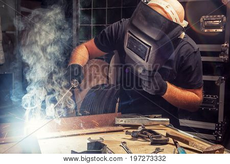 A bald strong man in a black T-shirt creates with his own hands a mettalical product and brews a metal welding machine many sparks fire and smoke