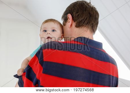 Happy proud young father having fun with newborn baby daughter, family portrait togehter. Dad with baby girl, love. Bonding, family, new life