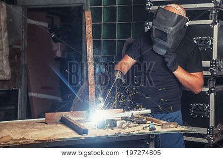 A bald man in black work clothes welds a metal arc welding machine in a production shop