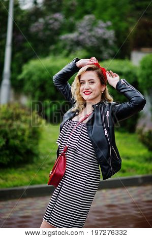 Portrait Of A Beautiful Bridesmaid In A Pretty Striped Dress Touching Her Red Hairband In The Park A