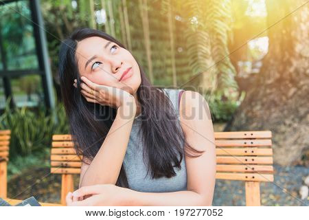 Thinking For The Future Concept. Asian Women Black Long Hair Adult Posture Thinks Action In The Gard