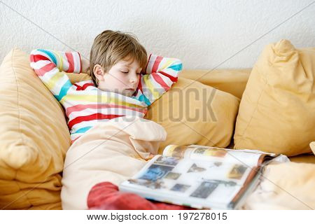 Little blonde school kid boy with glasses reading a book at home. Child interested in reading magazine for kids. Leisure for kids, building skills and education concept.
