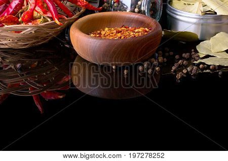Spices and herbs, bay leaf, red chili peppers and wooden bowl of chili flakes on black background with reflection
