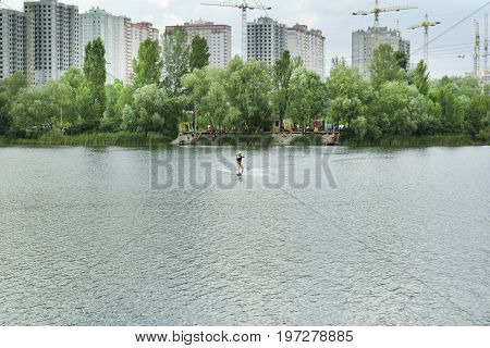Man is wakeboarding on a lake in the background of trees and construction