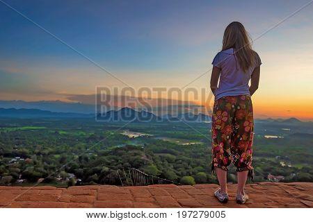 Female traveler is standing with on the edge Sigiriya and look on beautiful sunset Sri Lanka landscape
