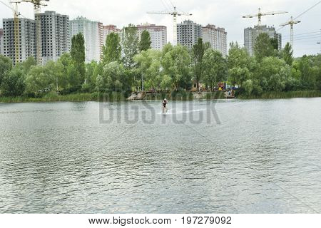 Men is engaged in wakeboarding on the background of construction