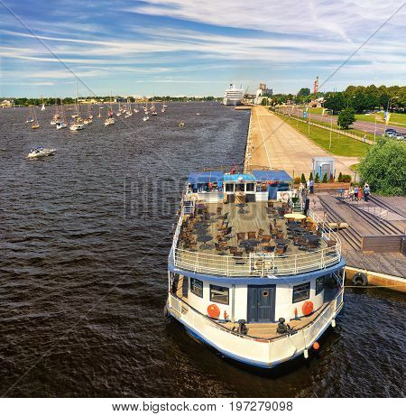 Panorama of a summer cafe on the deck of an old steamboat with a wheel on the background of a regatta on the Daugava River in summer.