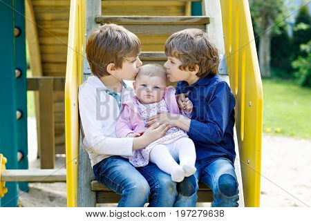 Two little happy kid boys with newborn baby girl, cute sister. Siblings on playground in summer or spring on mother's day. Brother holding baby girl on arm. Kids bonding. Family of three children