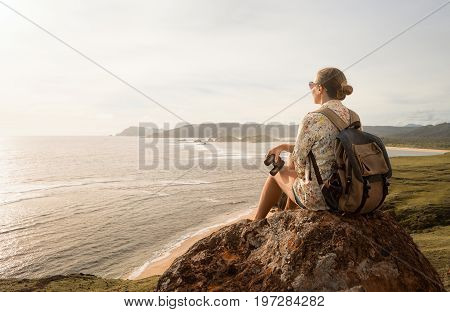 Happy woman tourist with backpack enjoying sunny coast view on sunrise. Traveling along mountains and coast freedom and active lifestyle concept.