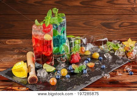 A beautiful composition of mojitos on a dark brown wooden background. Refreshing alcohol beverage with berries. A blueberry and a strawberry mojito. Ice cubes, fruits and lime slices. Copy space.