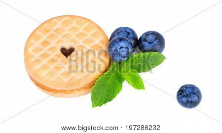 A view from above on a perfect light brown cookie with a heart. Juicy blueberries, mint leaves and crunchy biscuits isolated on a white background. Sugary and homemade organic snacks.