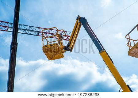 Hydraulic lift platform with bucket of yellow construction vehicle, heavy industry, blue sky and white clouds on background