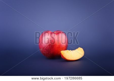 A whole fresh red nectarine and a little fruit piece. A refreshing nectarine on a saturated blue background. Natural, organic, healthful and nutritious nectarine full of vitamins.