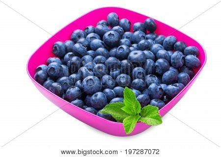 A close-up of freshly picked blueberries in a pink box isolated over the white background. A group of tasty and juicy blueberries and peppermint leaves in a saturated pink crate.