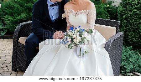 Groom And Bride Sitting On Couch And Holding Hands, Closeup. Bride In White Dress With Lace And Wedd