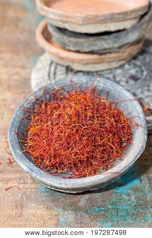 Dried Organic Red Saffron Spice In A Stone Bowl On Wooden Background
